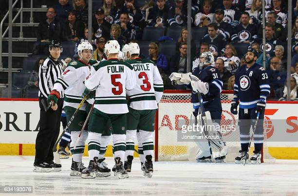Mike Reilly Christian Folin and Charlie Coyle of the Minnesota Wild celebrate a second period goal by teammate Jason Pominville against the Winnipeg...