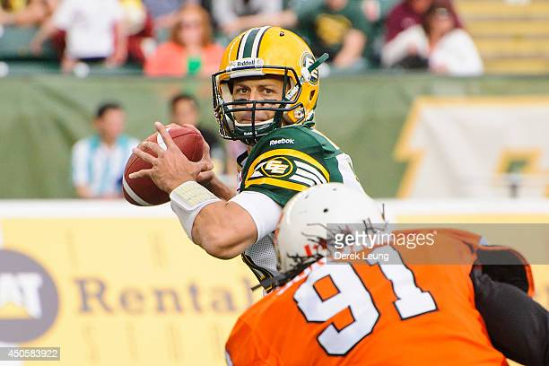 Mike Reilly of the Edmonton Eskimos looks up the field for a teammate to pass to as Brandon Jordan of the BC Lions chases him during a CFL game at...