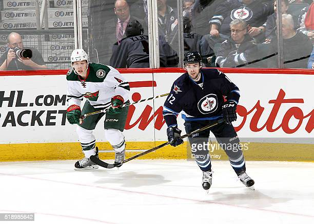 Mike Reilly of the Minnesota Wild and Drew Stafford of the Winnipeg Jets keep an eye on the play during second period action at the MTS Centre on...