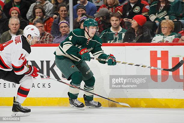 Mike Reilly of the Minnesota Wild passes the puck with Adam Henrique of the New Jersey Devils defending during the game on January 10 2016 at the...