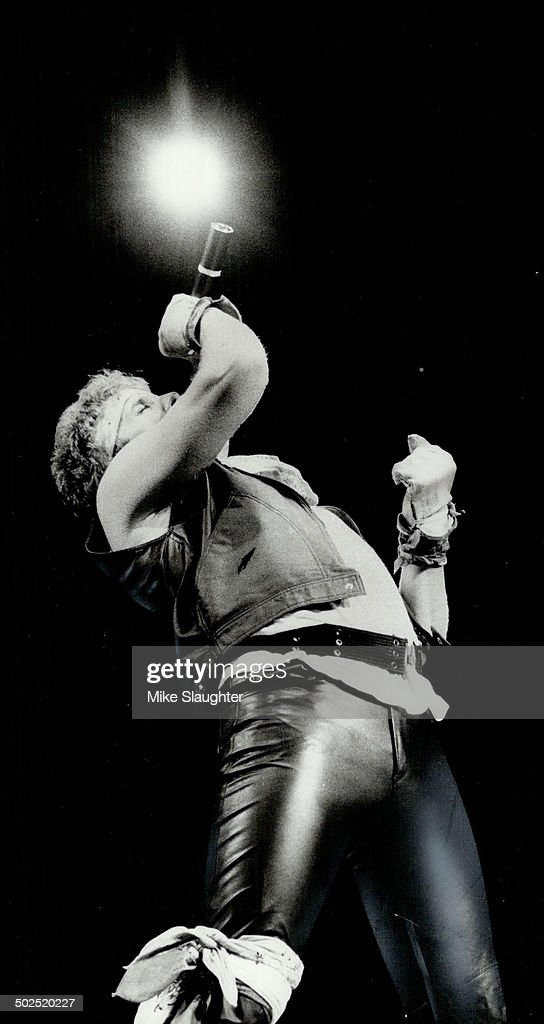 Mike Reno Loverboy's lead singer dressed in band's uniform of clinging black leather and bits of red and white cloth tied in various places delivered...