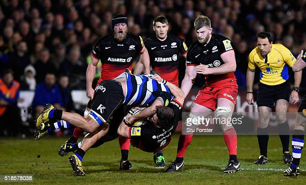Mike Rhodes of Saracens is upended by Leroy Houston and Chris Cook of Bath resulting in a yellow card for Chris Cook of Bath during the Aviva...