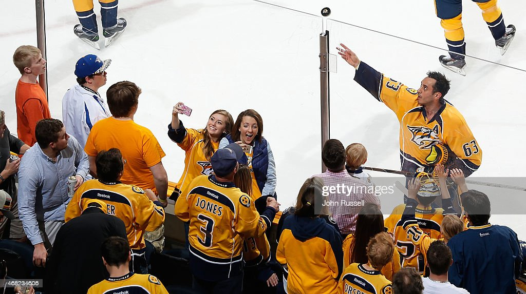 Mike Ribeiro of the Nashville Predators tosses a puck to fans during warmups prior to a game against the Vancouver Canucks during an NHL game at...