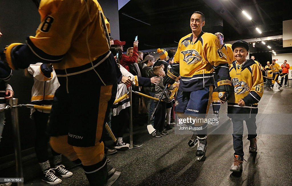 Mike Ribeiro of the Nashville Predators walks to the ice with his son Noah for warmups against the San Jose Sharks for his 1000th NHL game on...