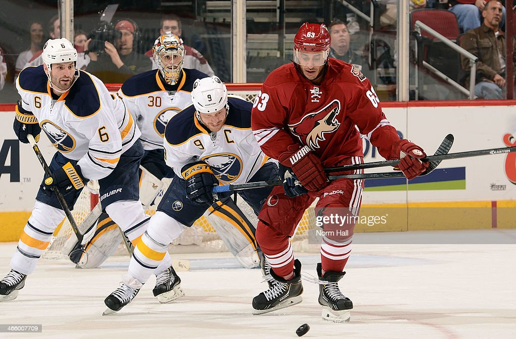 <a gi-track='captionPersonalityLinkClicked' href=/galleries/search?phrase=Mike+Ribeiro&family=editorial&specificpeople=203275 ng-click='$event.stopPropagation()'>Mike Ribeiro</a> #63 of the Phoenix Coyotes and <a gi-track='captionPersonalityLinkClicked' href=/galleries/search?phrase=Steve+Ott&family=editorial&specificpeople=210616 ng-click='$event.stopPropagation()'>Steve Ott</a> #9 of the Buffalo Sabres chase down a loose puck as Mike Weber #6 of the Sabres trail the play during the second period at Jobing.com Arena on January 30, 2014 in Glendale, Arizona.