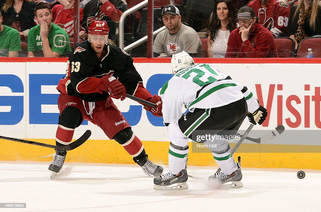 <a gi-track='captionPersonalityLinkClicked' href=/galleries/search?phrase=Mike+Ribeiro&family=editorial&specificpeople=203275 ng-click='$event.stopPropagation()'>Mike Ribeiro</a> #63 of the Phoenix Coyotes passes the puck around the defense of <a gi-track='captionPersonalityLinkClicked' href=/galleries/search?phrase=Antoine+Roussel&family=editorial&specificpeople=4202700 ng-click='$event.stopPropagation()'>Antoine Roussel</a> #21 of the Dallas Stars during the first period at Jobing.com Arena on February 4, 2014 in Glendale, Arizona.