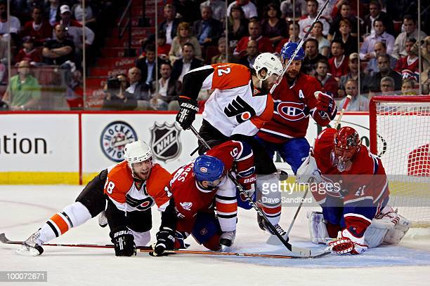 Mike Richards and Simon Gagne of the Philadelphia Flyers fight for the puck against Josh Gorges Brian Gionta and Jaroslav Halak of the Montreal...