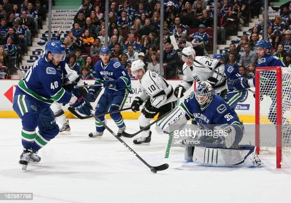 Mike Richards and Trevor Lewis of the Los Angeles Kings and Cory Schneider of the Vancouver Canucks look on as Maxim Lapierre of the Vancouver...