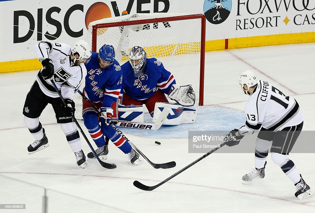 Mike Richards #10 of the Los Angeles Kings deflects a shot past Derek Stepan #21 of the New York Rangers towards Henrik Lundqvist #30 of the New York Rangers during the second period of Game Four of the 2014 NHL Stanley Cup Final at Madison Square Garden on June 11, 2014 in New York, New York.