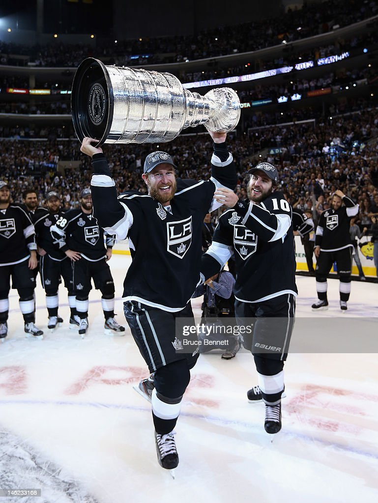 Mike Richards #10 of the Los Angeles Kings hands the Stanley Cup off to <a gi-track='captionPersonalityLinkClicked' href=/galleries/search?phrase=Jeff+Carter&family=editorial&specificpeople=227320 ng-click='$event.stopPropagation()'>Jeff Carter</a> #77 after the Kings defeated the New Jersey Devils 6-1 to win the Stanley Cup series 4-2 in Game Six of the 2012 Stanley Cup Final at Staples Center on June 11, 2012 in Los Angeles, California.