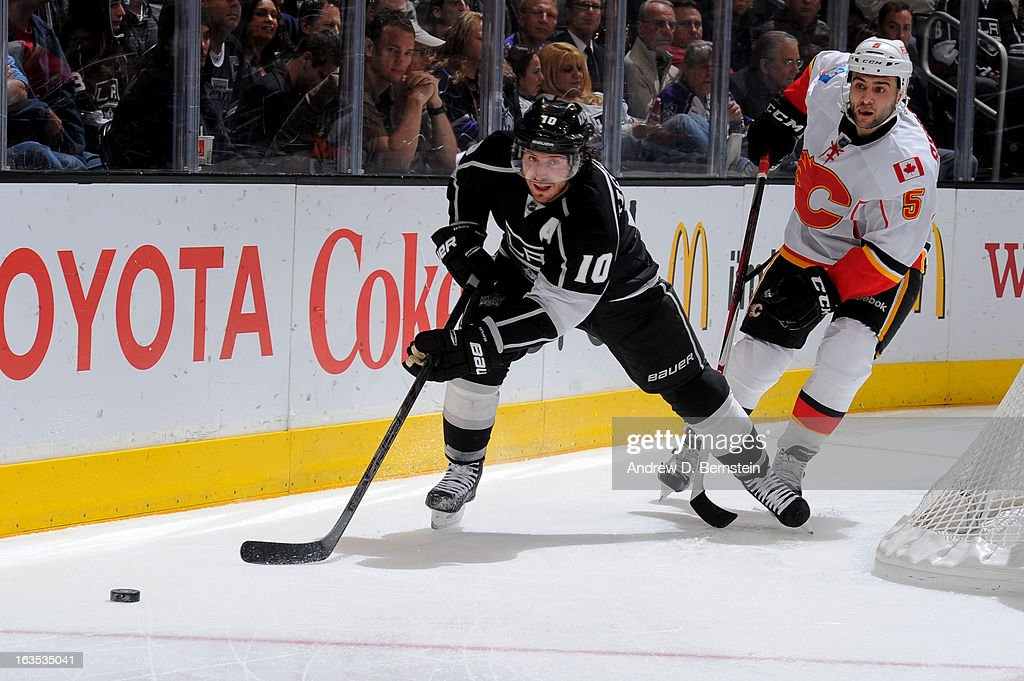 Mike Richards #10 of the Los Angeles Kings reaches for the puck against <a gi-track='captionPersonalityLinkClicked' href=/galleries/search?phrase=Mark+Giordano&family=editorial&specificpeople=696867 ng-click='$event.stopPropagation()'>Mark Giordano</a> #5 of the Calgary Flames at Staples Center on March 11, 2013 in Los Angeles, California.