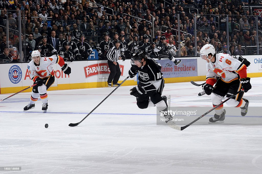 Mike Richards #10 of the Los Angeles Kings skates with the puck against <a gi-track='captionPersonalityLinkClicked' href=/galleries/search?phrase=Dennis+Wideman&family=editorial&specificpeople=575234 ng-click='$event.stopPropagation()'>Dennis Wideman</a> #6 of the Calgary Flames at Staples Center on October 21, 2013 in Los Angeles, California.