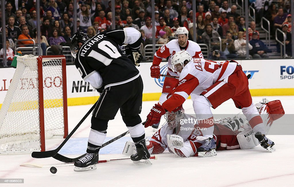 Mike Richards #10 of the Los Angeles Kings tries to get off a shot against Danny DeKeyser #65 and goalie Jimmy Howard #35 of the Detroit Red Wings at Staples Center on January 11, 2014 in Los Angeles, California.