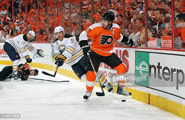 Mike Richards of the Philadelphia Flyers handles the puck against Derek Roy and MarcAndre Gragnani of the Buffalo Sabres in Game Seven of the Eastern...