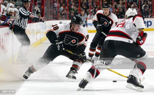 Mike Richards of the Philadelphia Flyers skates the puck past Sean Brown of the New Jersey Devils on November 30 2005 at the Wachovia Center in...