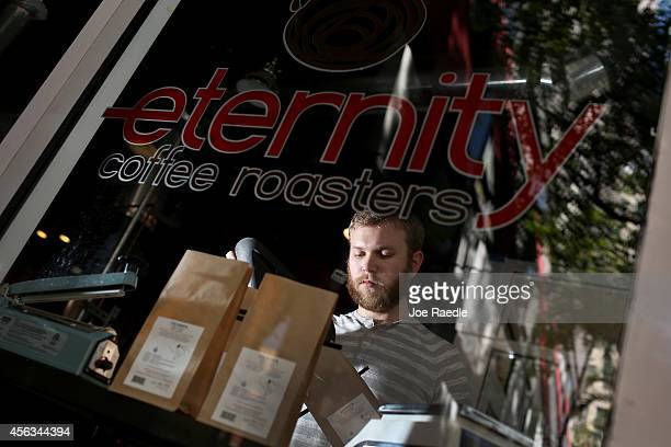 Mike Rodriguez bags roasted coffee beans at Eternity Coffee Roasters during National Coffee Day on September 29 2014 in Miami Florida The day is for...