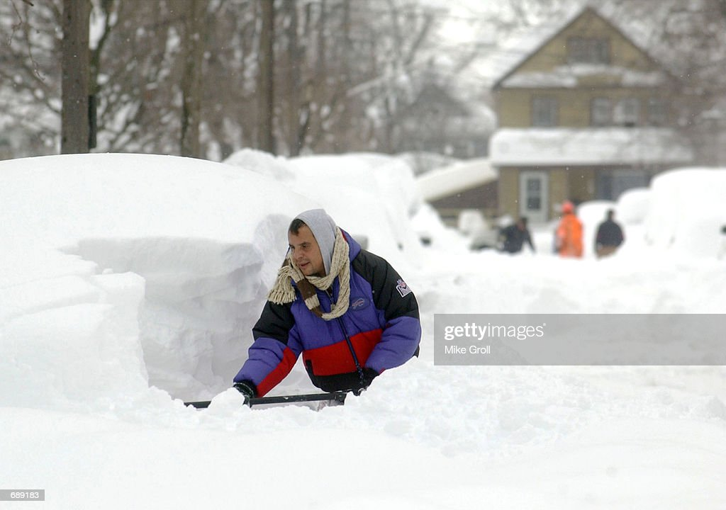 Mike Rodriguez digs his car out of a snow pile December 27 2001 in Buffalo NY Buffalo has been pounded by a lake effect snow storm resulting in six...