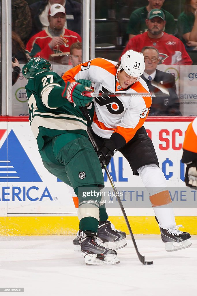 Mike Rupp of the Minnesota Wild collides with Jay Rosehill of the Philadelphia Flyers during the game on December 2 2013 at the Xcel Energy Center in...
