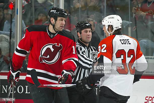 Mike Rupp of the New Jersey Devils and Riley Cote of the Philadelphia Flyers argue while Linesman Mark Shewchyk intervenes during the NHL game at the...
