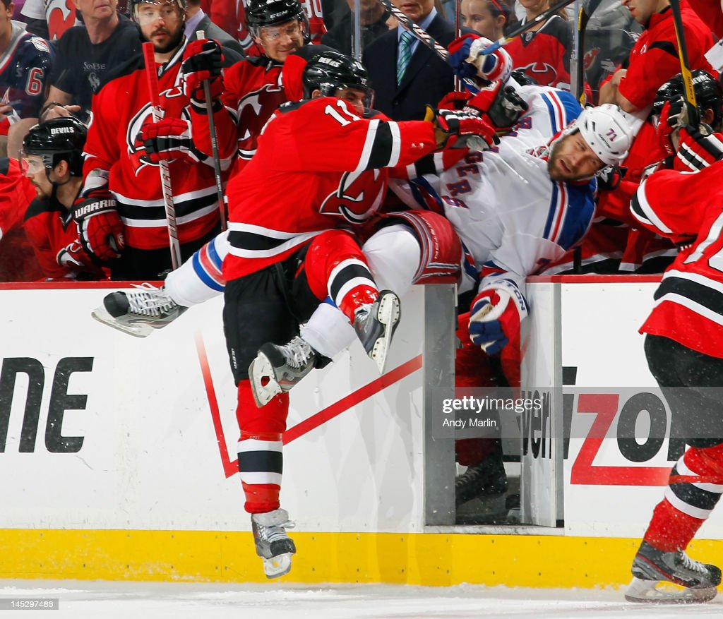 Mike Rupp #71 of the New York Rangers is checked over the boards by Stephen Gionta #11 of the New Jersey Devils in Game Six of the Eastern Conference Final during the 2012 NHL Stanley Cup Playoffs at the Prudential Center on May 25, 2012 in Newark, New Jersey.