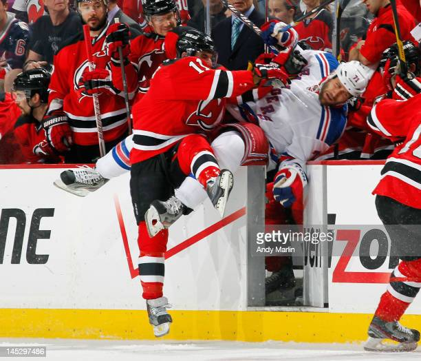 Mike Rupp of the New York Rangers is checked over the boards by Stephen Gionta of the New Jersey Devils in Game Six of the Eastern Conference Final...