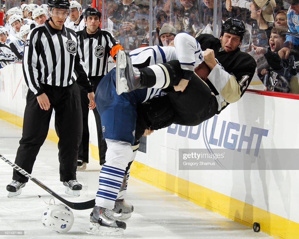Mike Rupp #17 of the Pittsburgh Penguins gets tripped up by <a gi-track='captionPersonalityLinkClicked' href=/galleries/search?phrase=Mike+Komisarek&family=editorial&specificpeople=213814 ng-click='$event.stopPropagation()'>Mike Komisarek</a> #8 of the Toronto Maple Leafs on December 8, 2010 at Consol Energy Center in Pittsburgh, Pennsylvania. Pittsburgh won the game 5-2.