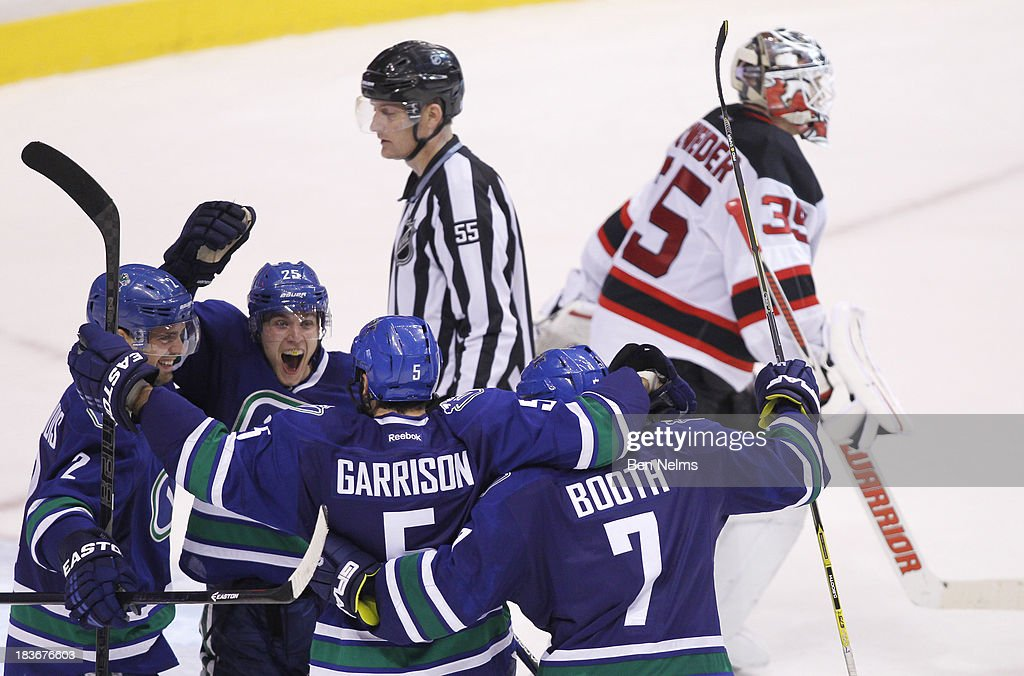 <a gi-track='captionPersonalityLinkClicked' href=/galleries/search?phrase=Mike+Santorelli&family=editorial&specificpeople=4517042 ng-click='$event.stopPropagation()'>Mike Santorelli</a> #25 celebrates teammate <a gi-track='captionPersonalityLinkClicked' href=/galleries/search?phrase=Jason+Garrison&family=editorial&specificpeople=2143635 ng-click='$event.stopPropagation()'>Jason Garrison</a>'s #5 goal against <a gi-track='captionPersonalityLinkClicked' href=/galleries/search?phrase=Cory+Schneider&family=editorial&specificpeople=696908 ng-click='$event.stopPropagation()'>Cory Schneider</a> of the New Jersey Devils during overtime of their NHL game at Rogers Arena on October 8, 2013 in Vancouver, British Columbia, Canada.