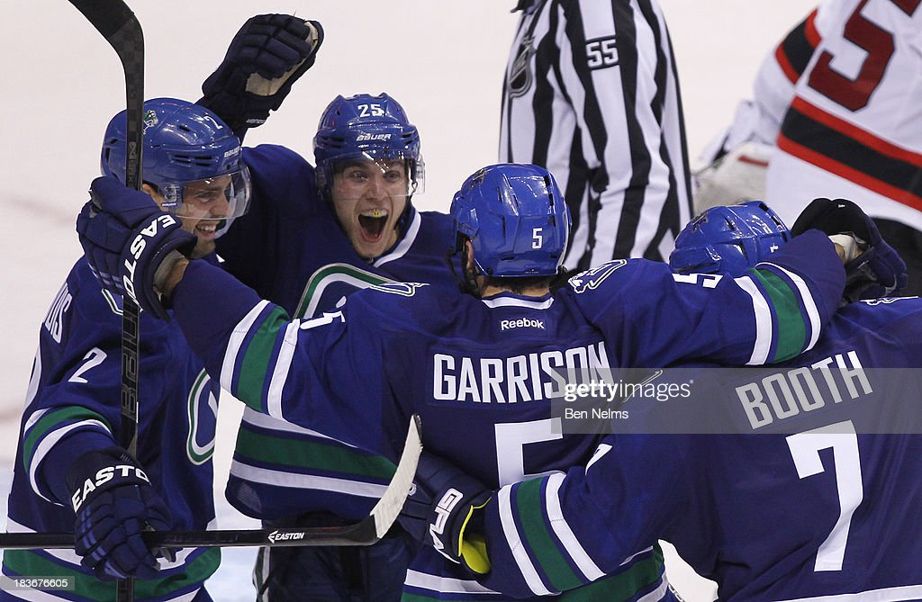 <a gi-track='captionPersonalityLinkClicked' href=/galleries/search?phrase=Mike+Santorelli&family=editorial&specificpeople=4517042 ng-click='$event.stopPropagation()'>Mike Santorelli</a> #25 celebrates teammate <a gi-track='captionPersonalityLinkClicked' href=/galleries/search?phrase=Jason+Garrison&family=editorial&specificpeople=2143635 ng-click='$event.stopPropagation()'>Jason Garrison</a>'s #5 goal against Cory Schneider of the New Jersey Devils during overtime of their NHL game at Rogers Arena on October 8, 2013 in Vancouver, British Columbia, Canada.