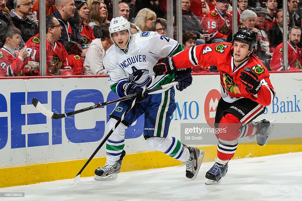 <a gi-track='captionPersonalityLinkClicked' href=/galleries/search?phrase=Mike+Santorelli&family=editorial&specificpeople=4517042 ng-click='$event.stopPropagation()'>Mike Santorelli</a> #25 of the Vancouver Canucks and <a gi-track='captionPersonalityLinkClicked' href=/galleries/search?phrase=Niklas+Hjalmarsson&family=editorial&specificpeople=2006442 ng-click='$event.stopPropagation()'>Niklas Hjalmarsson</a> #4 of the Chicago Blackhawks skate around the boards during the NHL game on December 20, 2013 at the United Center in Chicago, Illinois.