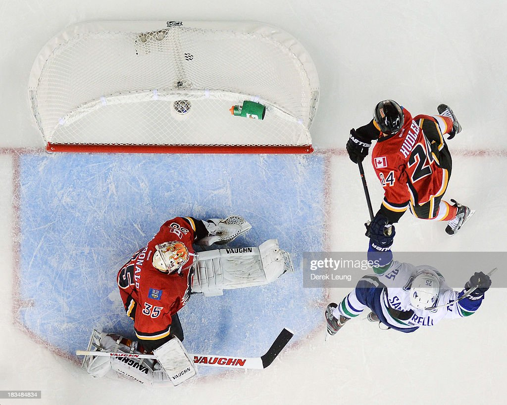<a gi-track='captionPersonalityLinkClicked' href=/galleries/search?phrase=Mike+Santorelli&family=editorial&specificpeople=4517042 ng-click='$event.stopPropagation()'>Mike Santorelli</a> #25 of the Vancouver Canucks celebrates scoring the OT goal against Joey MacDonald #35 of the Calgary Flames during the Flames' home opening NHL game at Scotiabank Saddledome on October 6, 2013 in Calgary, Alberta, Canada. The Vancouver Canucks won 5-4 in OT.