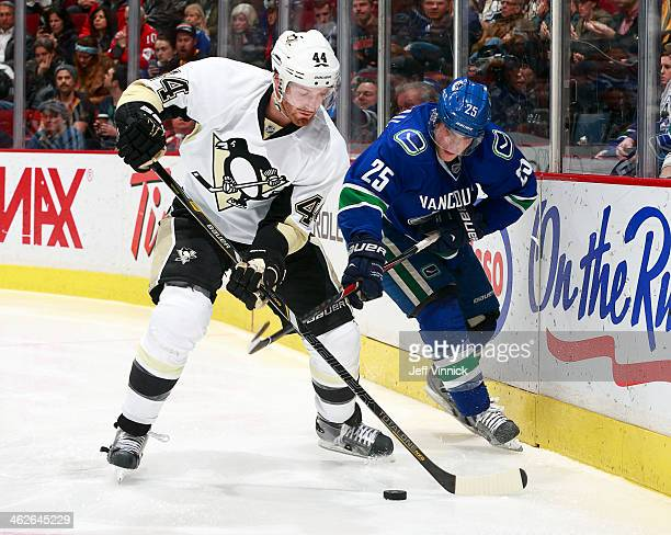 Mike Santorelli of the Vancouver Canucks checks Brooks Orpik of the Pittsburgh Penguins during their NHL game at Rogers Arena January 7 2014 in...