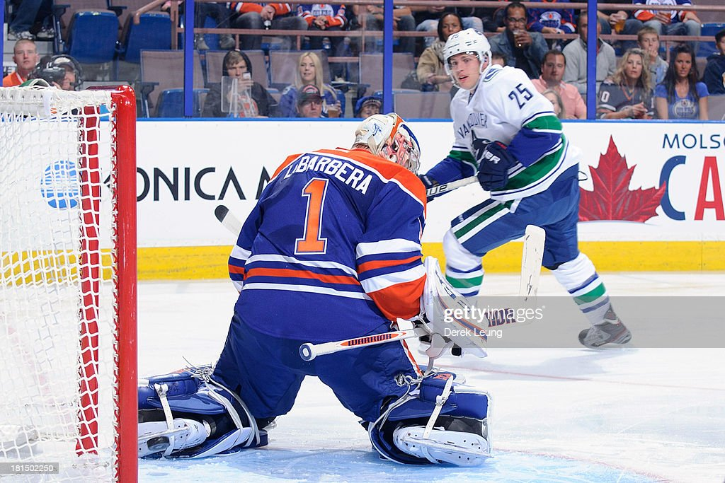 <a gi-track='captionPersonalityLinkClicked' href=/galleries/search?phrase=Mike+Santorelli&family=editorial&specificpeople=4517042 ng-click='$event.stopPropagation()'>Mike Santorelli</a> #25 of the Vancouver Canucks shoots the puck past Jason Labarbera #1 of the Edmonton Oilers during a preseason NHL game at Rexall Place on September 21, 2013 in Edmonton, Alberta, Canada.