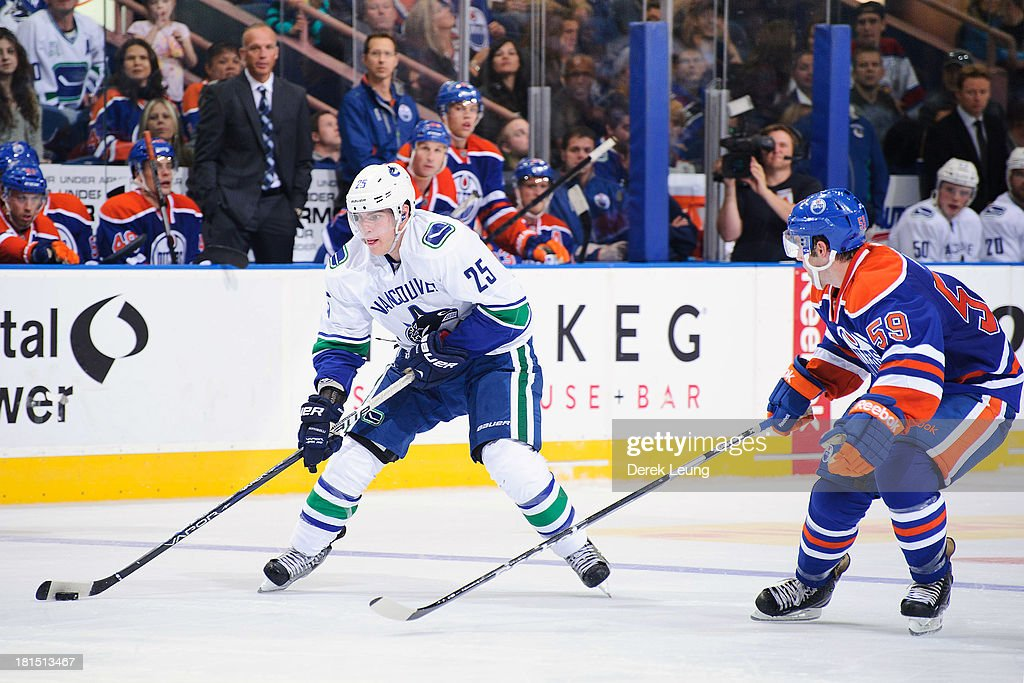 <a gi-track='captionPersonalityLinkClicked' href=/galleries/search?phrase=Mike+Santorelli&family=editorial&specificpeople=4517042 ng-click='$event.stopPropagation()'>Mike Santorelli</a> #25 of the Vancouver Canucks skates with the puck against Brad Hunt #59 of the Edmonton Oilers during a preseason NHL game at Rexall Place on September 21, 2013 in Edmonton, Alberta, Canada.