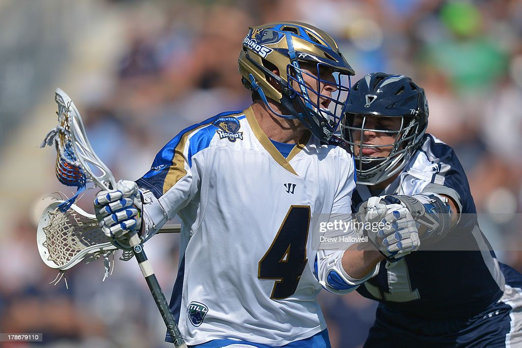 Mike Sawyer #4 of the Charlotte Hounds is checked by Jeff Reynolds #21 of the Chesapeake Bayhawks during the MLL Championship at PPL Park on August 25, 2013 in Chester, Pennsylvania.