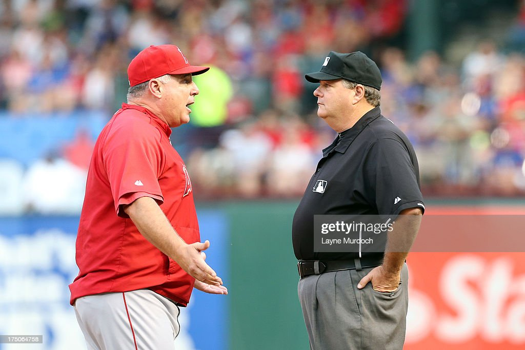 Mike Scioscia, manager of the Los Angeles Angels argues a call with 1st base umpire Jerry Layne in a game against the Texas Rangers of Anaheim on July 30, 2013 at the Rangers Ballpark in Arlington in Arlington, Texas.