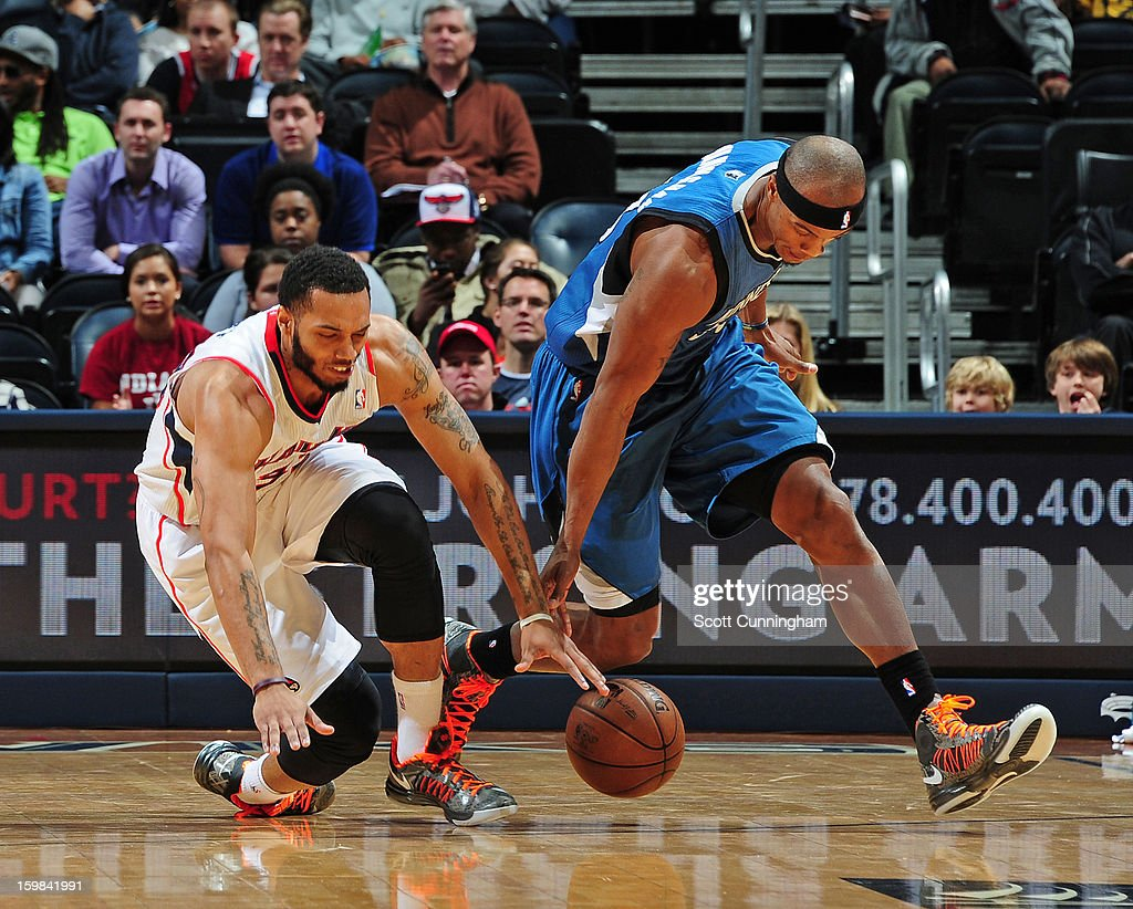 Mike Scott #32 of the Atlanta Hawks and Dante Cunningham #33 of the Minnesota Timberwolves battle for a loose ball on January 21, 2013 at Philips Arena in Atlanta, Georgia.