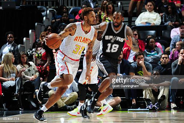 Mike Scott of the Atlanta Hawks dribbles the ball against Rasual Butler of the San Antonio Spurs on October 14 2015 at Philips Arena in Atlanta...