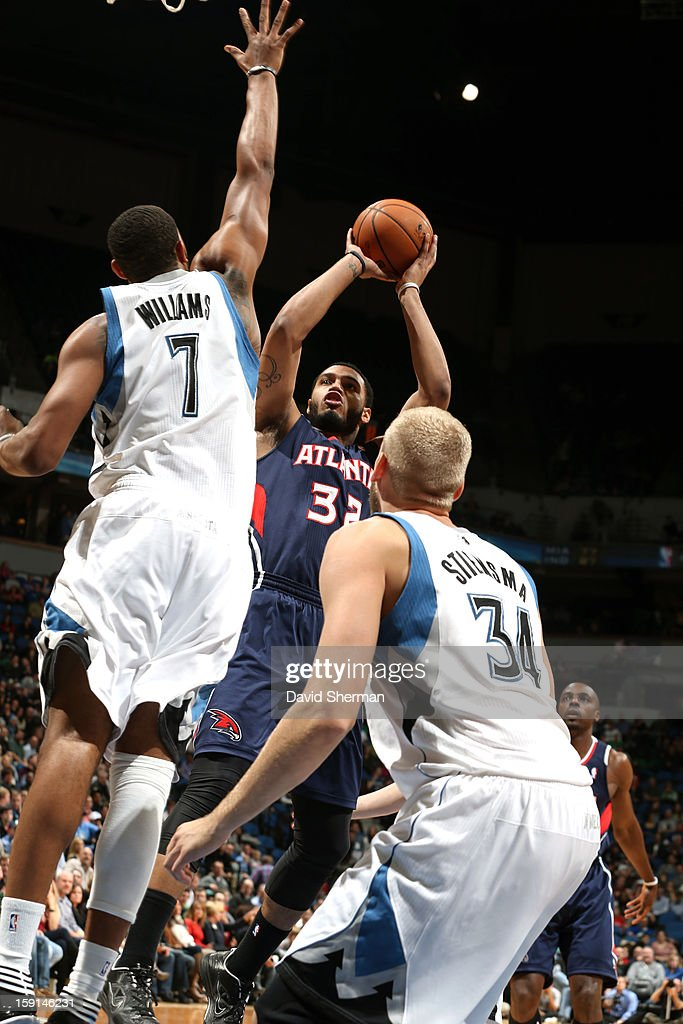 Mike Scott #32 of the Atlanta Hawks goes up for a fade away shot in traffic against Derrick Williams #7 and Greg Stiemsma #34 of the Minnesota Timberwolves during the game on January 8, 2013 at Target Center in Minneapolis, Minnesota.