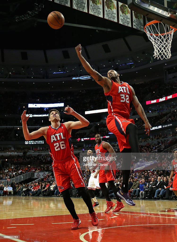 Mike Scott #32 of the Atlanta Hawks leaps for a rebound over teammate Kyle Korver #26 against the Chicago Bulls at the United Center on February 11, 2014 in Chicago, Illinois. The Bulls defeated the Hawks 100-85.