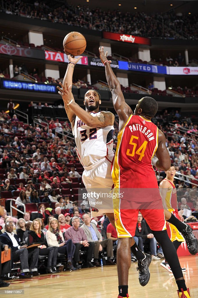 Mike Scott #32 of the Atlanta Hawks puts up a shot over <a gi-track='captionPersonalityLinkClicked' href=/galleries/search?phrase=Patrick+Patterson&family=editorial&specificpeople=2928099 ng-click='$event.stopPropagation()'>Patrick Patterson</a> #54 of the Houston Rockets on December 31, 2012 at the Toyota Center in Houston, Texas.