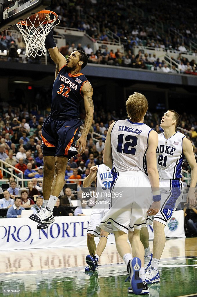 Mike Scott of the University of Virginia Cavaliers drives by Miles Plumlee and Kyle Singler of the Duke Blue Devils guards in their quarterfinal game...