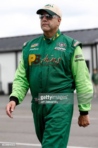 Mike Senica driver of the Chevrolet stands in the garage area during practice for the NASCAR Camping World Truck Series Overton's 150 at Pocono...