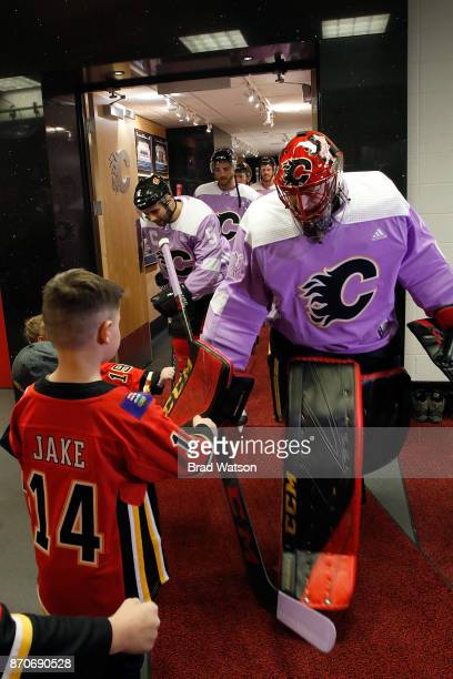 Mike Smith and teammates of the Calgary Flames fist bump young fans for Hockey Fights Cancer before an NHL game against the New Jersey Devils on...