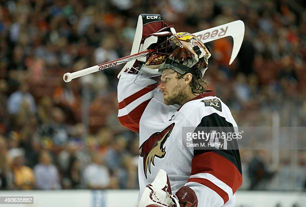Mike Smith of the Arizona Coyotes adjusts his helmet during the first period of a game against the Anaheim Ducks at Honda Center on October 14 2015...