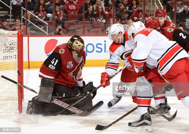 Mike Smith of the Arizona Coyotes makes a save against Derek Ryan of the Carolina Hurricanes during the first period at Gila River Arena on March 5...