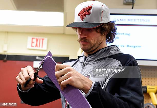 Mike Smith of the Arizona Coyotes prepares his hockey stick with purple tape in support of the NHL's leaguewide Hockey Fights Cancer initiative prior...