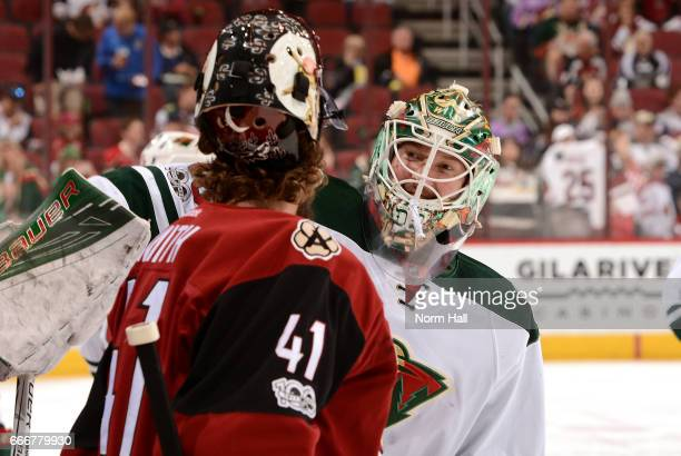 Mike Smith of the Arizona Coyotes talks with former teammate Devan Dubnyk of the Minnesota Wild during pregame at Gila River Arena on April 8 2017 in...
