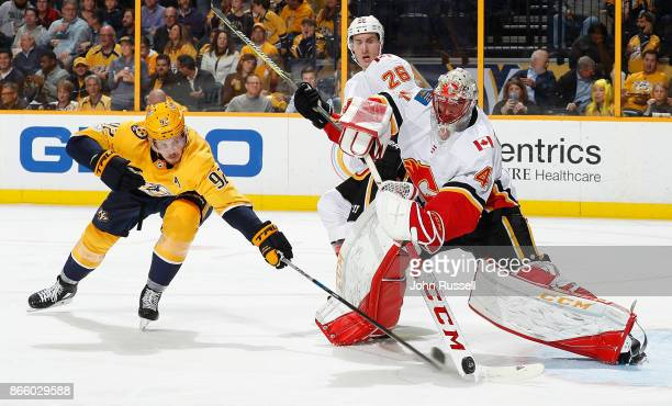 Mike Smith of the Calgary Flames clears the puck against Ryan Johansen of the Nashville Predators during an NHL game at Bridgestone Arena on October...