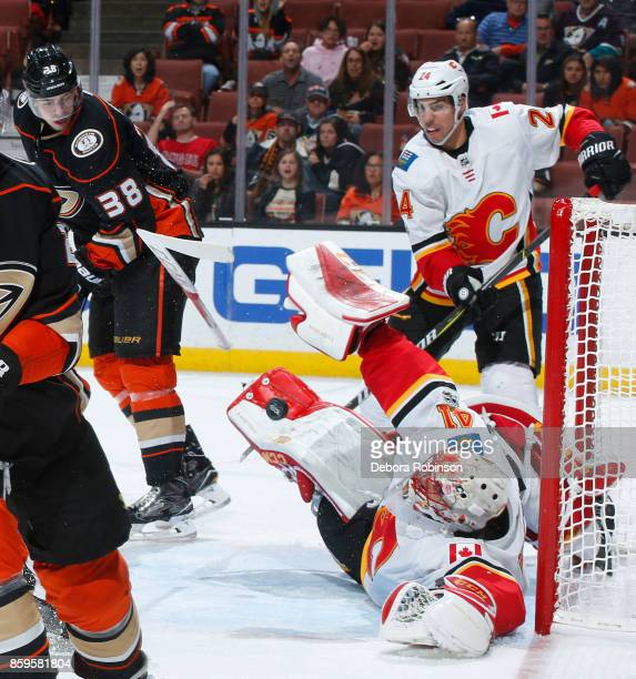 Mike Smith of the Calgary Flames makes a save against Derek Grant of the Anaheim Ducks with help from Travis Hamonic during the game on October 9...