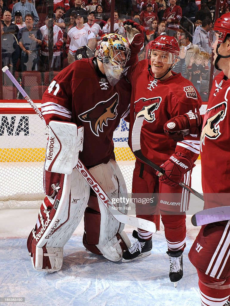 Mike Smith #41 of the Phoenix Coyotes and teammate <a gi-track='captionPersonalityLinkClicked' href=/galleries/search?phrase=Jeff+Halpern&family=editorial&specificpeople=206583 ng-click='$event.stopPropagation()'>Jeff Halpern</a> #14 celebrate a win against the Detroit Red Wings at Jobing.com Arena on October 19, 2013 in Glendale, Arizona.